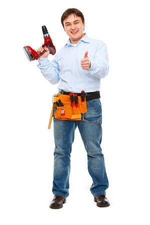 Full length portrait of construction worker with drill showing thumbs up photo