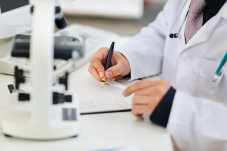 docs: Closeup on hands of medical doctor working with documents
