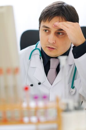 centrality: Concerned medical doctor working on computer at office Stock Photo