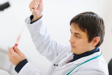 centrality: Medical doctor working with blood sample in laboratory