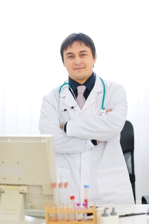 certitude: Portrait of medical doctor standing at table Stock Photo