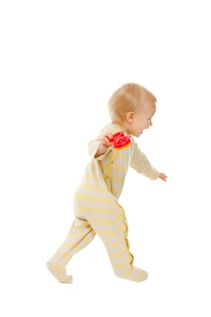 Cheerful baby running with rattle on white background 스톡 콘텐츠