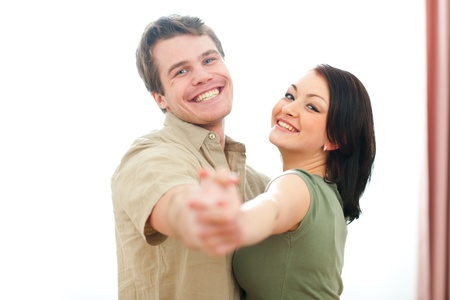 Smiling young couple dancing at home photo