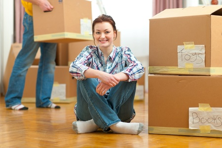 packaging move: Portrait of girl and boyfriend carrying boxes to new house in background