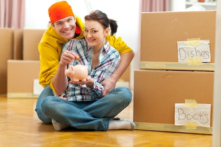 Young couple among boxes putting coin in piggy bank Stock Photo - 12356654