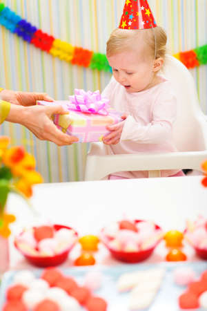 Surprised baby receiving present on first birthday photo