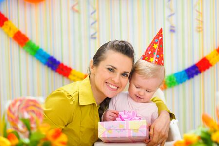 Portrait of mother with baby celebrating first birthday photo