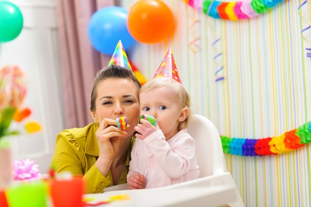 Baby and mother blowing into party horn photo