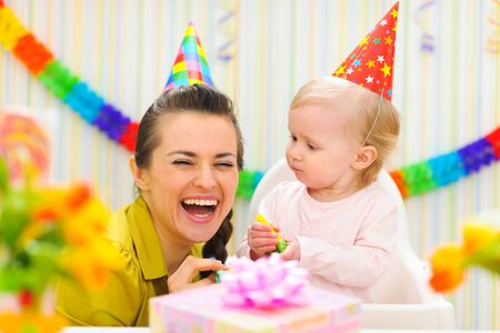 Happy mother celebrating first birthday of her baby photo