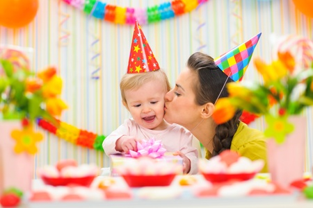 birthday celebration: Mother kissing her happy while baby checking present Stock Photo