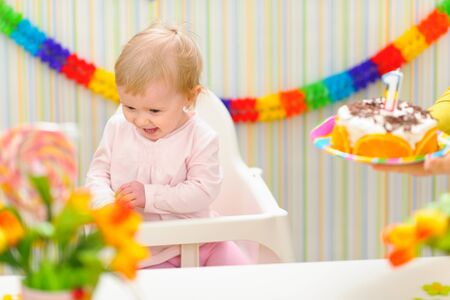 Baby happy and embarrassed receiving birthday cake Stock Photo - 12356351
