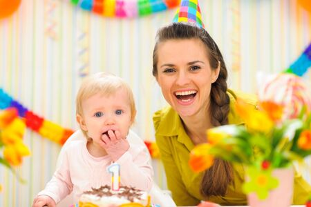 first birthday: Portrait of mother with baby eating birthday cake