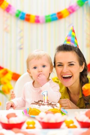 1st birthday: Portrait of mother with baby enjoying first birthday cake