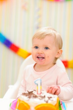 Portrait of eat smeared baby with birthday cake photo