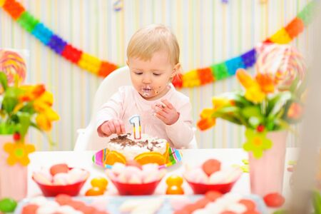 Portrait of eat smeared baby eating birthday cake photo