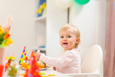 first birthday: Portrait of eat smeared kid eating birthday cake Stock Photo