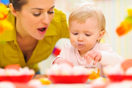 Baby celebrating first birthday with mom photo