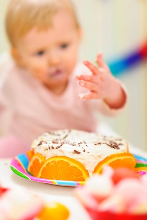 eat smeared baby: Closeup on birthday cake and eat smeared baby in background anonymous