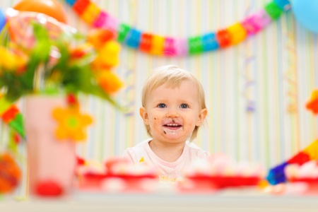 Portrait of eat smeared baby celebrating first birthday Stock Photo - 12356153