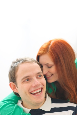 Red hair young woman whispering in boyfriends ear photo