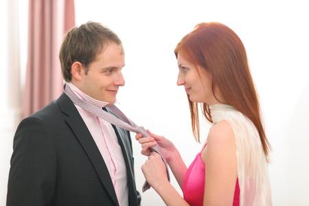 tie necktie: Red hair young woman helping tie necktie