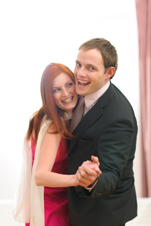 Formally dressed happy couple having fun dancing photo