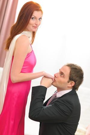 handkuss: Junger Mann im Anzug küssen die Hände von roten Haaren Frau im Abendkleid