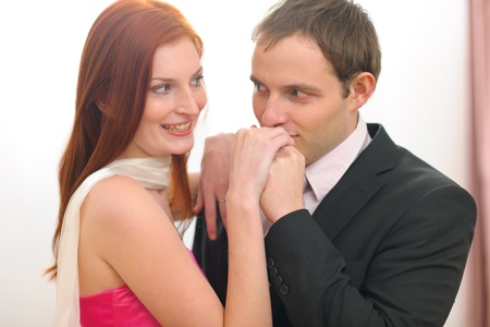 amorous woman: Young man in suit kissing hands of red hair woman in evening dress Stock Photo