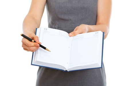Closeup on pen pointing in open notepad in hands of female Stock Photo - 12354625