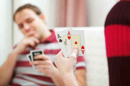 Closeup on hands with playing cards and man in background photo