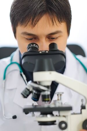 Closeup on medical doctor looking in microscope Stock Photo - 12637365