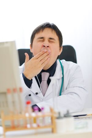 yaw: Tired medical doctor yawing