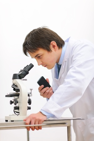 Researcher looking in microscope and making notes on voice recorder photo