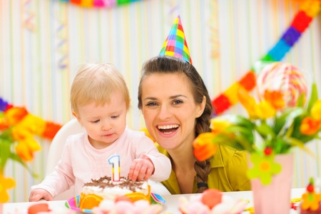 first birthday: Portrait of mother and baby with birthday cake