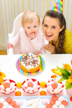 Portrait of happy mom and baby with birthday cake photo