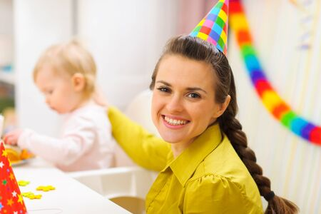 Portrait of happy mother celebrating baby first birthday photo