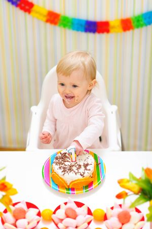 eat smeared: Happy eat smeared baby eating first birthday cake Stock Photo