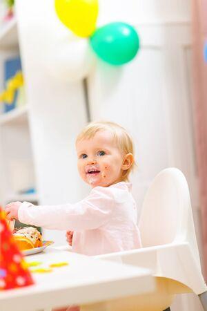 eat smeared baby: Beb� sonriente en celebraci�n del primer cumplea�os