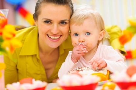 eat smeared baby: Feliz madre y el beb� en primera fiesta fiesta de cumplea�os Foto de archivo