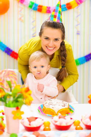 eat smeared baby: Smiling mother and eat smeared baby on birthday celebration party Stock Photo