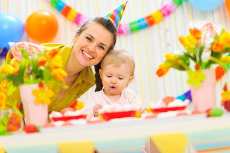 smeared baby: Smiling mom and eat smeared baby on birthday celebration party Stock Photo