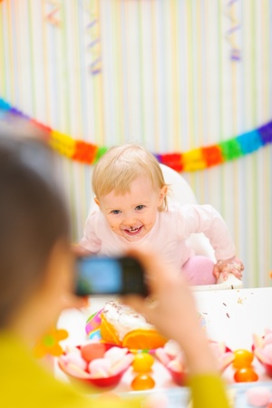 Mother making photos of happy baby on first birthday party photo