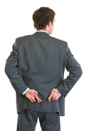 Business man standing back to camera with crossed fingers photo
