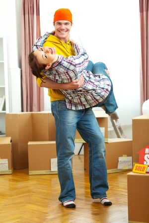 Young couple having fun while moving to new house photo