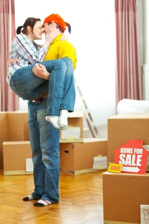Home for sale sign with sold sticker and guy holding girlfriend in background Stock Photo - 12637585