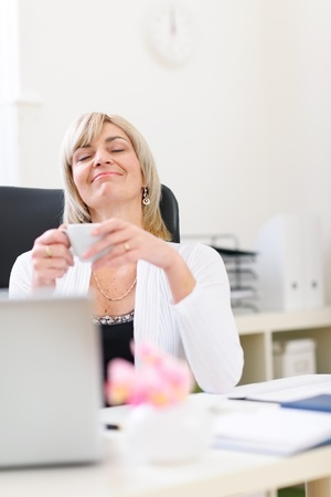 stargaze: Senior business woman having cup of coffee and dreaming about vacation Stock Photo