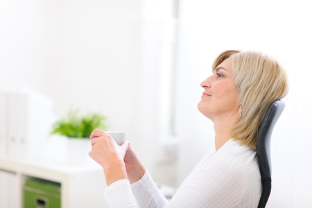 stargaze: Portrait of dreaming senior business woman with cup of coffee