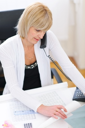 Senior architect woman speaking phone and looking on blueprints Stock Photo - 12637800