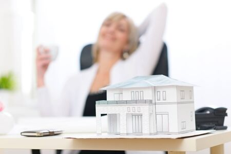 building planners: Closeup on scale model of house and happy architect woman in background
