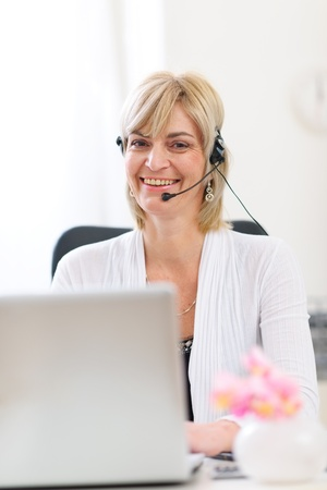 Smiling senior business woman with headset working on laptop photo